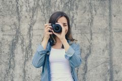 Close up front view portrait of woman taking photo. She is dressed in white t-shirt and jeans shirt. Focus is on the lens, focus c stock photography