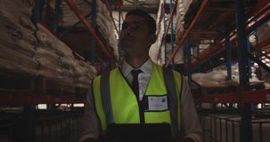 Male warehouse worker patrolling warehouse corridor at night 4k stock footage