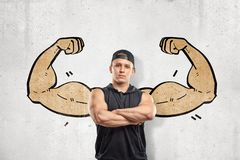 Close up front view of young athletic man with arms crossed, standing against wall with drawing of big muscular arms. Right from behind his back. Build perfect royalty free stock photography
