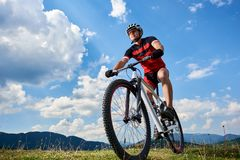 Close-up front view of young athletic sportsman cyclist in professional sportswear riding a bike royalty free stock image