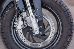 A close-up of the front wheel of a motorcycle with brakes royalty free stock photography