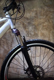 Close up front wheel tire of mountain bike against grungy cement Stock Images