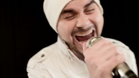 Close-up frontman vocalist rock pop with a stylish beard in white clothes and a hat with a microphone in his hands. Expressively aggressively singing in the stock footage