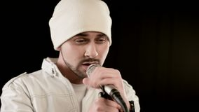 Close-up frontman vocalist rock pop with a stylish beard in white clothes and a hat with a microphone in his hands. Expressively aggressively singing in the stock video
