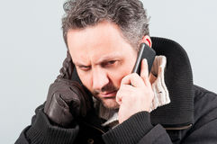 Close-up of frowning man in winter clothes Stock Images
