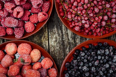 Close up of frozen berries in bowls on wooden background. Top view. Royalty Free Stock Image