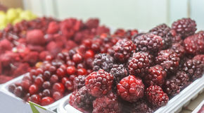 Close-up of frozen fruit in supermarket. Blackberry in focus, blurred Raspberrie Royalty Free Stock Image