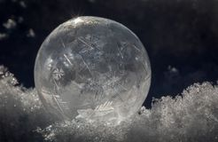 Close-up of Frozen Soap Bubble with Ice Crystals in Snow. Still-life Close-up of Frozen Soap Bubble with Ice Crystals in Snow with light and shadows Stock Photography