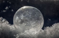 Close-up of Frozen Soap Bubble with Ice Crystals in Snow. Still-life Close-up of Frozen Soap Bubble with Ice Crystals in Snow with light and shadows Royalty Free Stock Image