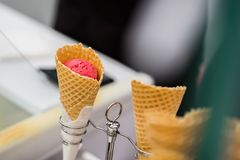 Close-up of fruit, natural, strawberry Ice-cream red color in waffle cone. Selective focus. Real scene in the store. Selective focus. Concept of delicacy Stock Photos