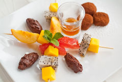 Close-up of fruit salad. A close-up of fruit salad dessert on white plate with chocolate truffles and caramel sauce Stock Image