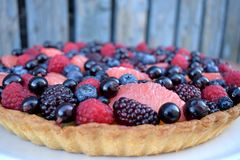 Close up Fruit Tart Dessert Homebaked Fresh Raspberry Blueberry Grapefruit Summer Berries. Homemade Cake. Top view. Wooden Rustic. Close up Fruit Tart Dessert Royalty Free Stock Image