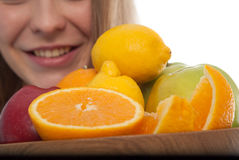 Close up of fruits in wooden bowl. Healthy. Kiwi, Lemon, orange, apples composed in wooden bowl and held by young woman. Stock Image