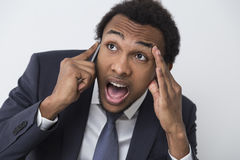 Close up of frustrated African American man. Close up of a frustrated and stressed out African American businessman on his phone with an open mouth and a hand Royalty Free Stock Images