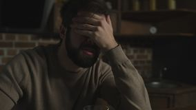 Close up of frustrated drunk man. Left and forgotten. Close up of young bearded man drinking alcohol while touching his face and expressing sadness stock video footage