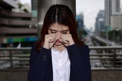 Close up frustrated stressed young Asian businesswoman crying closed face with her hands at outside office. stock photos
