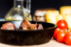 Tasty roasted chicken giblets in pan. Close up frying pan with delicious roasted chicken giblets and other food in background. Selective focus Royalty Free Stock Photo