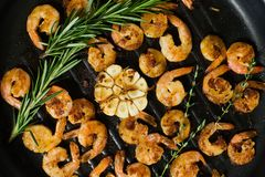Close-up of a frying pan with fried king prawns and sprigs of rosemary and thyme. royalty free stock photo