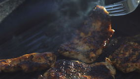 Close up of frying and turning over meat on grill stock video