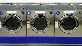 Close up full frame of industrial washing machines for public use in laundromat/ laundrette. Full frame view on rows of industrial washing machines for public royalty free stock image