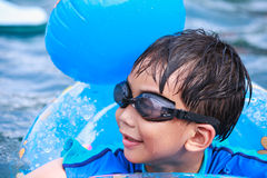 Close up funny asian boy with swim tube in pool. Outdoor. Royalty Free Stock Photos