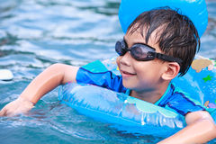 Close up funny asian boy with swim tube in pool. Outdoor. Stock Photo