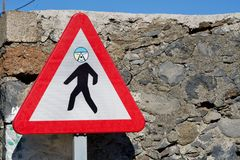 Funny attention pedestrian road sign. Close-up of a funny attention pedestrian road sign with an individual face stock images