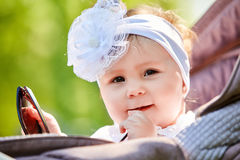 Close-up of the funny baby girl sitting in the stroller and holds sunglasses. Cute little girl in the white dress and with bow on her head. Sunshiny summer day Royalty Free Stock Photography