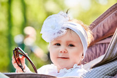 Close-up of the funny baby girl sitting in the stroller and holds sunglasses. Cute little girl in the white dress and with bow on her head. Sunshiny summer day Royalty Free Stock Images