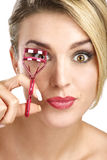 Close up of a funny beautiful girl using eyelash curler. On white Stock Photos