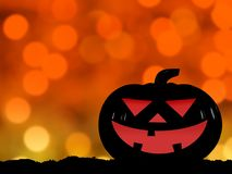 Silhouette of halloween pumpkin on hill with defocused orange and yellow lights  Royalty Free Stock Photography