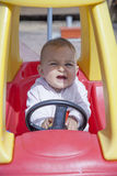 Close-up of funny little girl driving toy car Stock Images
