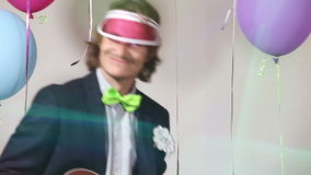 Close up of funny man playing ukulele in photo booth stock video