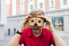 Close-up of funny man using cardboard virtual reality goggle outdoors Stock Photo
