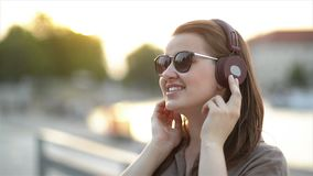 Close Up Funny Portrait Of Young Pretty Girl Listening Music On Big Earphones, Wearing Cute Sunglasses, Posing At City. Center at Sunny Summer Day. HD stock video footage