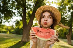 Close up of funny young girl in summer hat spending time at the park,. Showing slice of a watermelon stock photo
