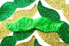 St Patrick`s Mustaches. Close up of a fuzzy green mustache on top of other glitter mustaches stock photo