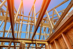 Close-up of gables roof on stick built home under construction and blue sky. New build roof with wooden truss, post and beam framework. Timber frame house, real royalty free stock image