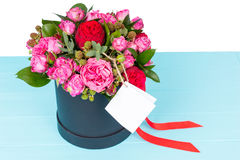 Close up of gallant bouquet of pink and red roses with a blank g. Ift tag with copy space and red ribbon in a circular black box. Valentines and anniversary Stock Photos