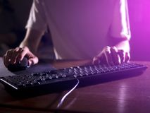 Close up gamer hands on the keyboard playing video games in night Stock Photo