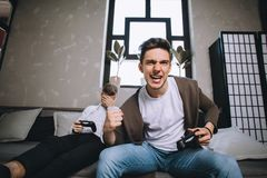 Gamers playing party. Close up of gamers sitting in the small room on the couch. The winner is yelling and enjoying his win while another guy is lying on the Stock Photos