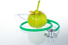 Close up garcinia cambogia and stethoscope with reflection on wh. Garcinia cambogia fresh fruit and stethoscope with reflection, isolated on white. Garcinia Stock Images