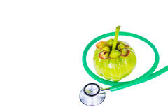 Close up garcinia cambogia and stethoscope on white background. Garcinia cambogia fresh fruit and stethoscope, isolated on white. Garcinia atroviridis is a Stock Photography