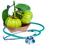 Close up garcinia cambogia and stethoscope on white background. Stock Photo