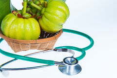 Close up garcinia cambogia and stethoscope on white background. Stock Photography