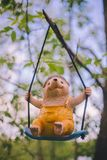 Close-up garden figurine decor - a cheerful hedgehog in yellow clothes sitting on a swing - hanging on a tree branch stock photo