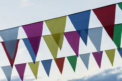 Close-up garland of colorful flags of triangular shape, pennants against blue sky. City street holiday. Modern. Background, pattern, wallpaper or banner design Royalty Free Stock Photos