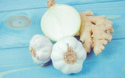 Garlic bulbs, ginger and onion on blue wooden table. Natural medicine. Royalty Free Stock Photo