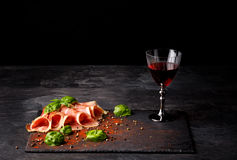 Close-up of a gastronomy composition. A full wine glass, prosciutto and basil leaves on a black background. Copy space. Close-up of fantastic sliced prosciutto Stock Photo