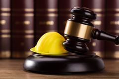 Close-up Of Gavel And Hard Hat. Close-up Of Gavel And Yellow Hard Hat In Courtroom royalty free stock photography